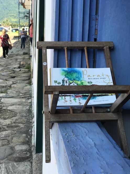 Janela azul com livro sobre Paraty